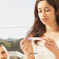 Hispanic-couple-with-pregnancy-test-looking-worried